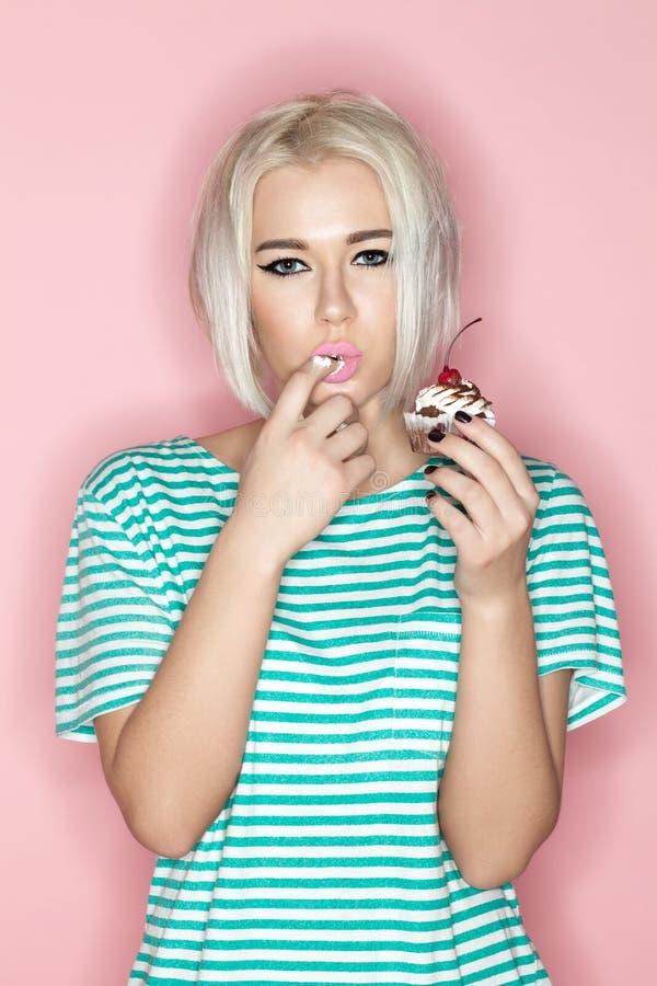 Louro que come o cak em um fundo cor-de-rosa imagem de stock