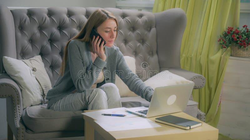 Louro que fala no smartphone, fazendo anotações nas cartas e no portátil fotos de stock royalty free