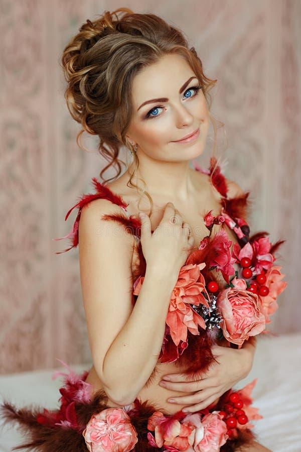 Louro sensual bonito da menina em um roupa de banho das flores vermelhas, cl imagem de stock royalty free