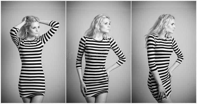 Louro 'sexy' atrativo no vestido apertado preto e branco do ajuste que levanta provocatively interno retrato da mulher sensual foto de stock royalty free