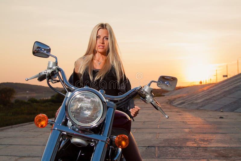 Louro 'sexy' novo que senta-se em sua motocicleta imagem de stock