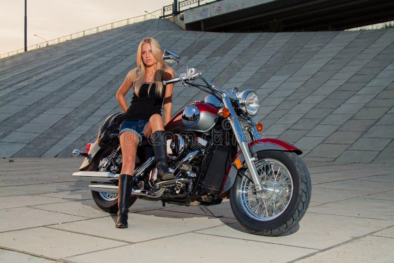 Louro 'sexy' novo que senta-se em sua motocicleta fotografia de stock