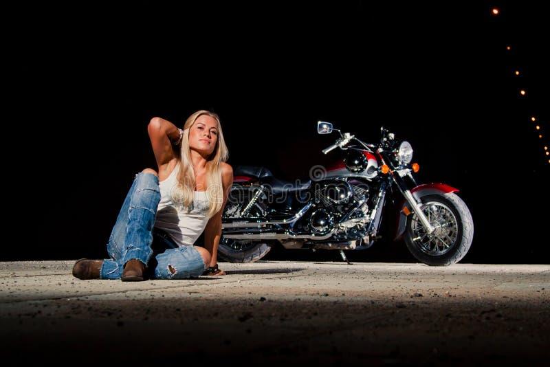 Louro 'sexy' que senta-se perto de sua motocicleta imagem de stock royalty free