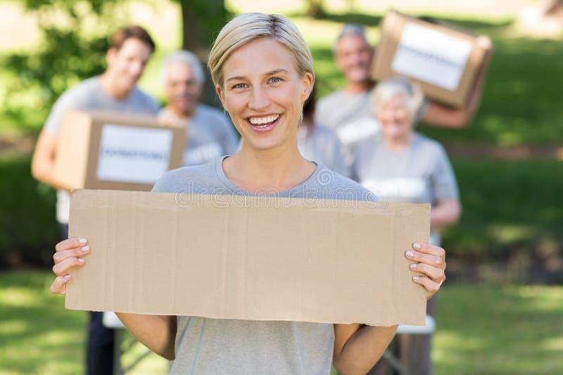 Louro voluntário feliz que guarda a placa fotos de stock
