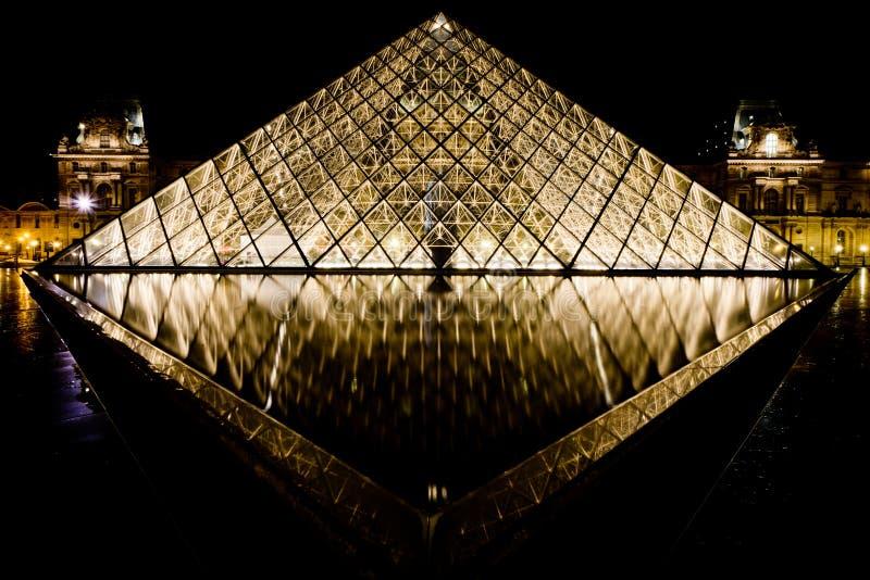 Louvre di Musee a Parigi di notte fotografia stock libera da diritti
