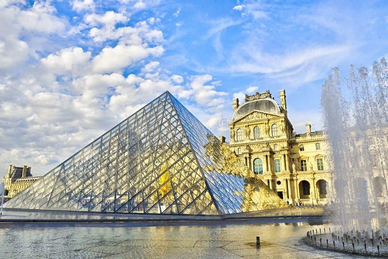 Louvre facade med glastriangel från stora konstmuseum royaltyfria bilder