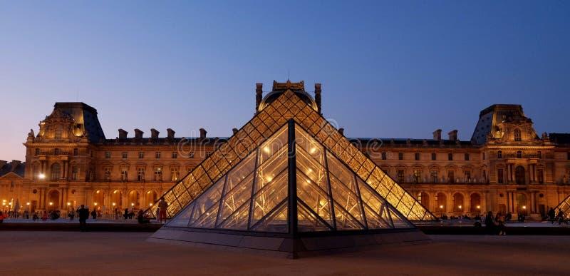 Louvre i ostrosłup póżno możemy wieczór z światłami Paris france zdjęcie royalty free