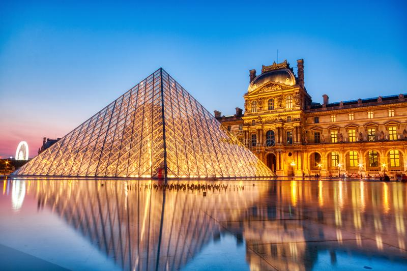 Louvre Museum at Night, Paris. Editorial:.PARIS, FRANCE - JULY 6: The Louvre Pyramid at dusk during the Michelangelo Pistoletto stock photos
