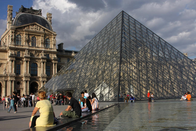 Louvre pyramid. Tourists visit the Louvre pyramid in Paris royalty free stock photos