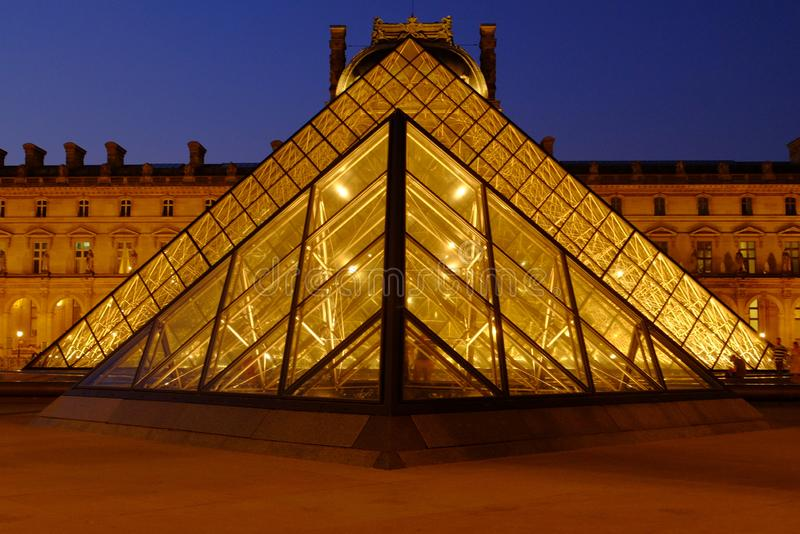 The Louvre and the Pyramid late may evening with lights.Paris, France. royalty free stock image