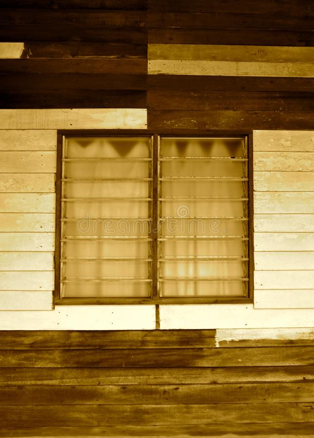 Sepia image of louvred windows in a basic wooden dwelling. Louvred glass shutter windows in a basic timber building. The horizontal wooden slats are weathered royalty free stock photos