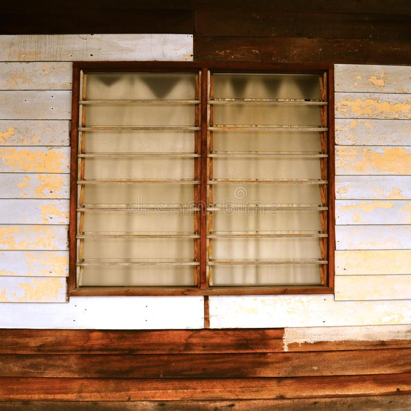 Louvred windows in a rustic boarded dwelling. Louvred glass shutter windows in a basic timber building. The horizontal wooden slats are weathered and partially stock photography