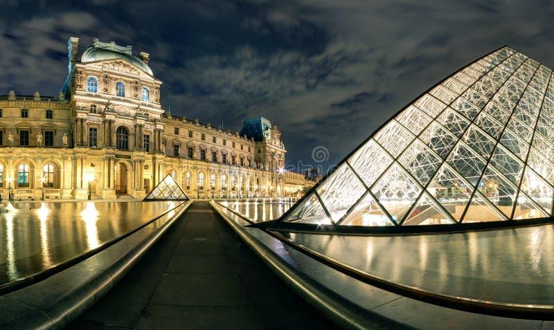 Louvremuseet på natten i Paris royaltyfria foton