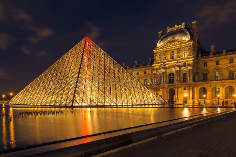 Louvremuseum en de Piramide in Parijs, Frankrijk, bij nachtillumi stock afbeelding