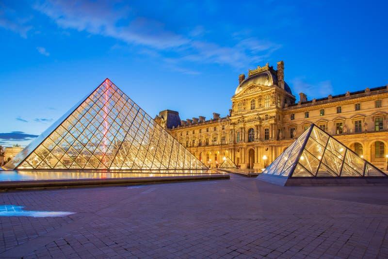 Louvremuseum i Paris på skymning i Frankrike royaltyfria bilder