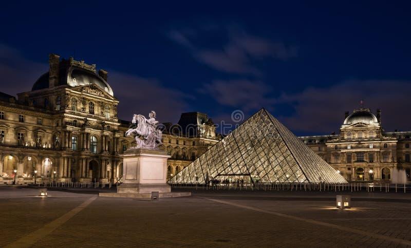 Louvremuseum med pyramiden i skymning royaltyfri foto
