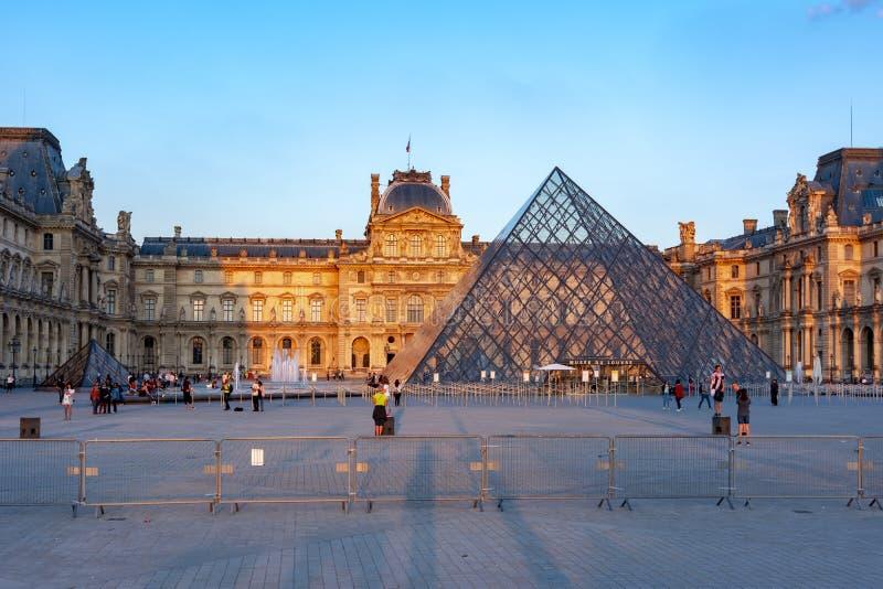 Louvremuseum och pyramid på solnedgången, Paris, Frankrike royaltyfri bild