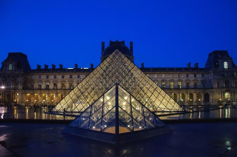 Louvremuseum p? skymning i vintern Paris arkivfoto