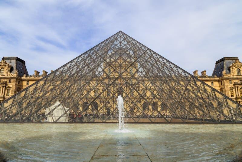 Louvremuseumpyramid och historisk byggnad royaltyfria bilder