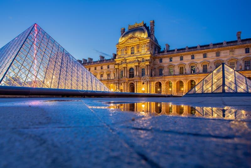 LouvreParis museum med reflexion på natten i Paris, Frankrike royaltyfria foton