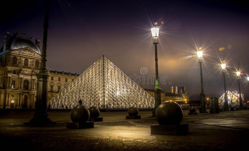Louvrepiramide, Parijs bij nacht stock afbeeldingen