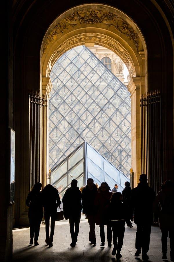 Louvrepyramid med konturer av folk i förgrund Mest besökte konstmusemet i världen och en historisk monument, med 35.000 royaltyfri fotografi