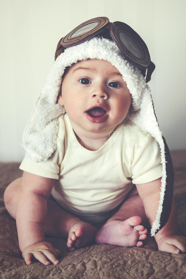 Lovable baby. Portrait of a lovable 5 months baby in funny pilot hat, toned image royalty free stock images
