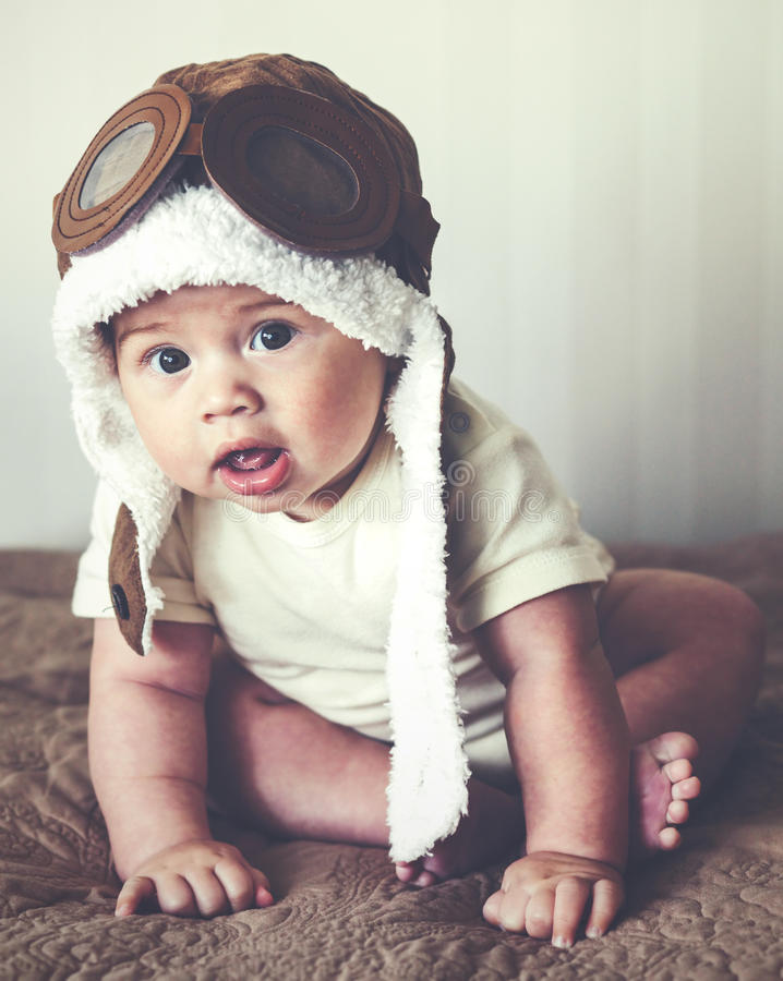 Lovable baby. Portrait of a lovable 5 months baby in funny pilot hat, toned image royalty free stock photography