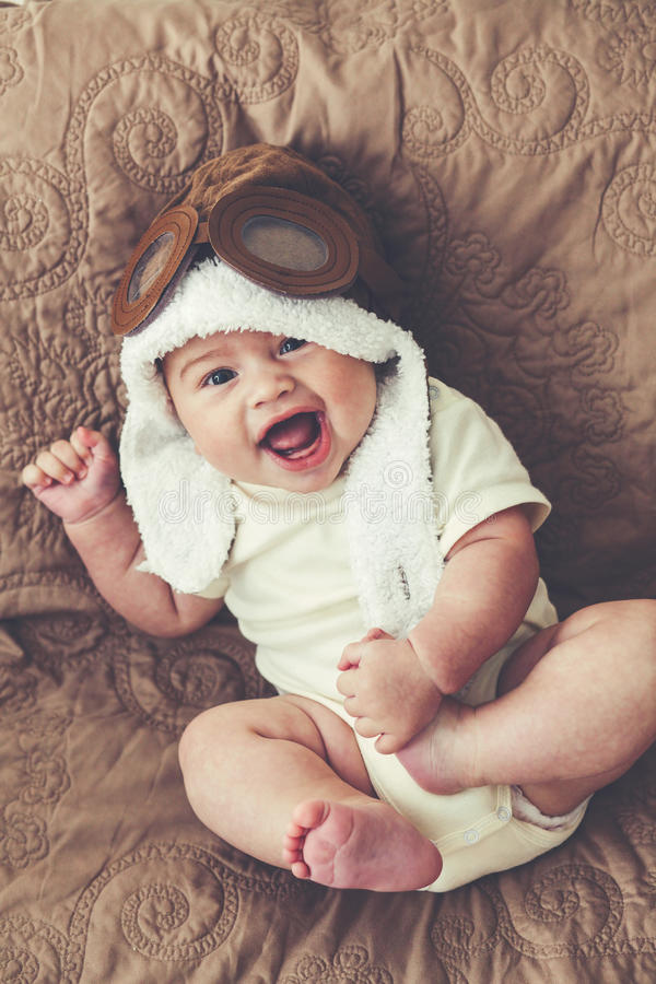 Lovable baby. Portrait of a lovable 5 months baby in funny pilot hat, toned image stock image