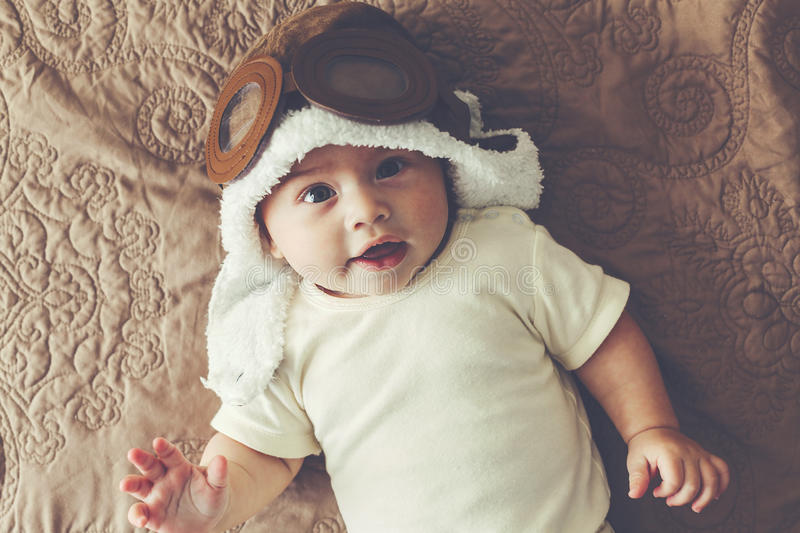Lovable baby. Portrait of a lovable 5 months baby in funny pilot hat, toned image stock photos