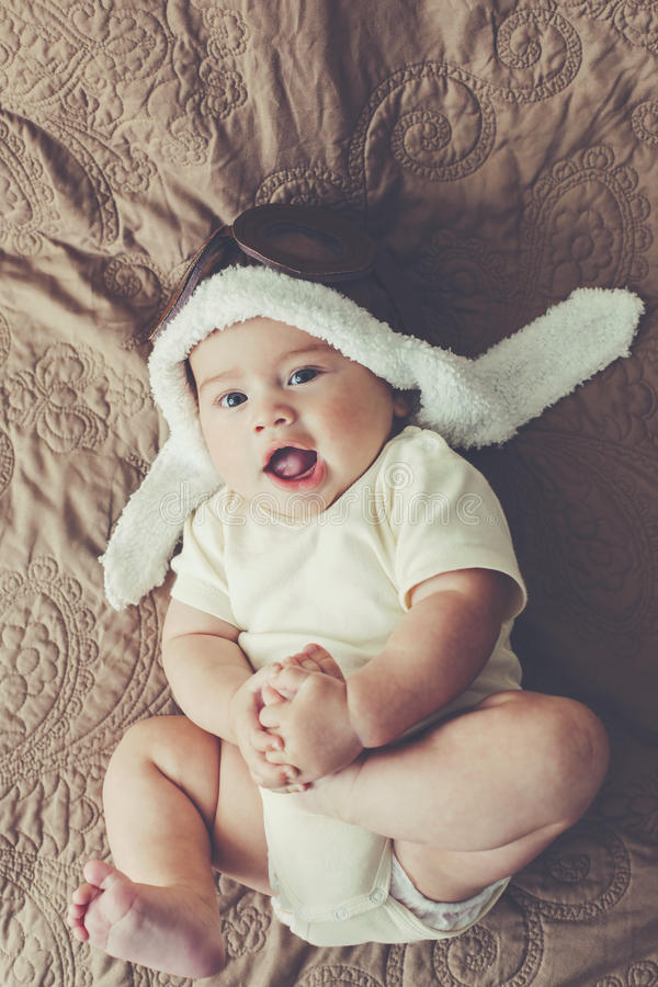 Lovable baby. Portrait of a lovable 5 months baby in funny pilot hat, toned image stock photography