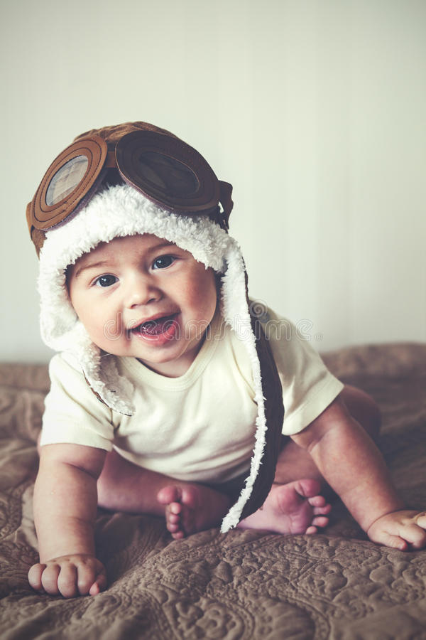 Lovable baby. Portrait of a lovable 5 months baby in funny pilot hat, toned image stock images