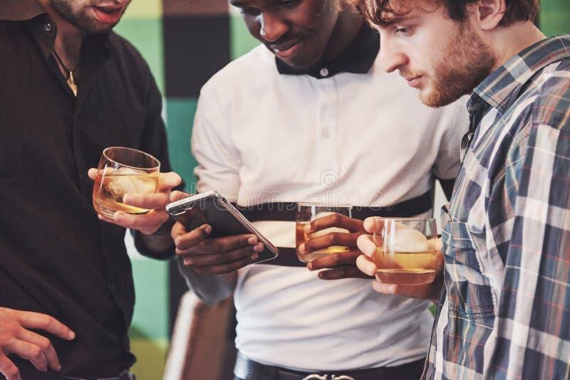 Lovande ungt mång- etniskt folk som firar och dricker whiskyrostat bröd, klockagrej arkivfoto