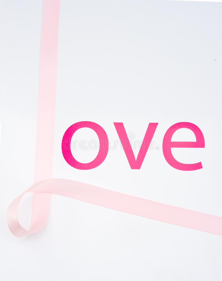 Love. Pink ribbon looped to complete the word love against a plain background. There is just a hint of breast cancer awareness by including the ribbon royalty free stock image