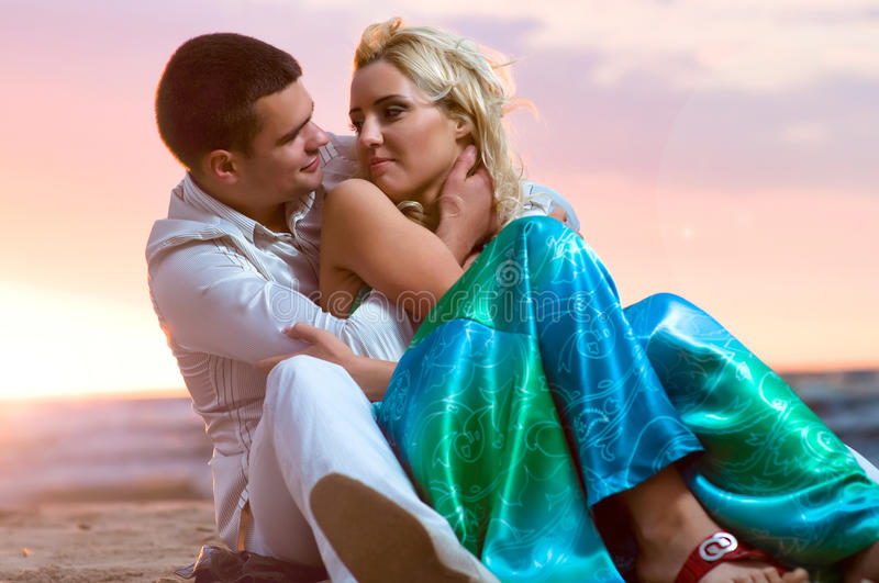 In love. Young couple in love near the sea at sunset royalty free stock photography
