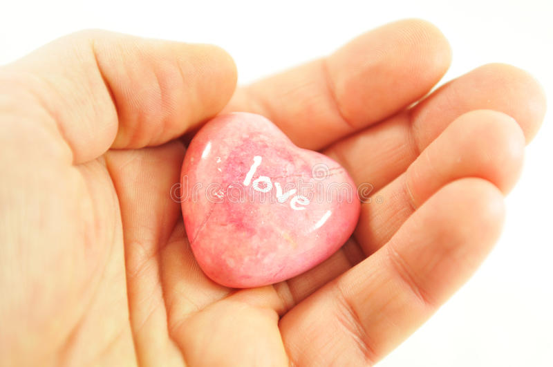 Love. Matrimonial concept with hand holding a heart shaped stone with love message royalty free stock photo