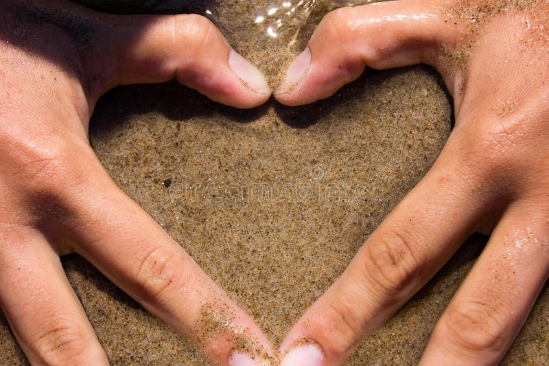 Love. Image of woman's hands made in the form of heart on the sand beach royalty free stock photos