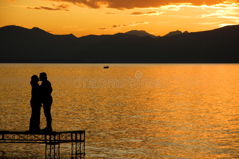 Love. A romantic kiss at sunset, a sign of love royalty free stock image