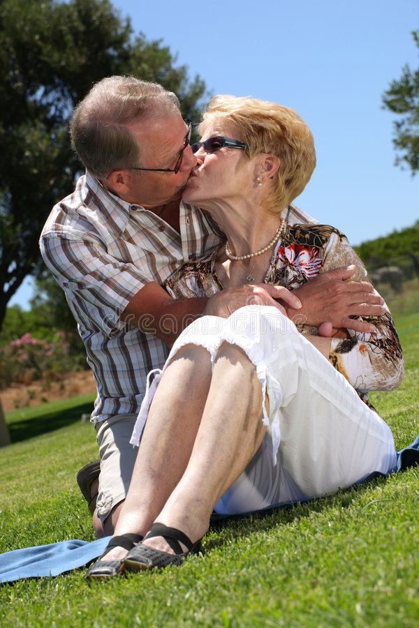 So in love!. Romantic senior couple kissing outdoors royalty free stock photo