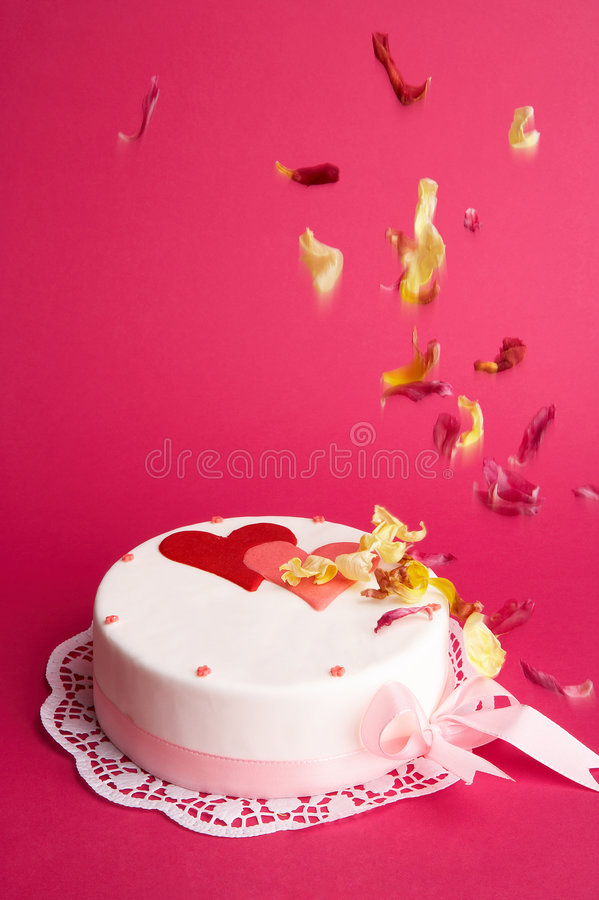 Love is in the air. White cake with red and pink hearts and falling blossoms royalty free stock photos