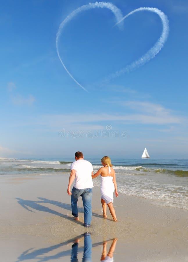 Love in the Air. Couple walking on beach under heart skywriting stock photos