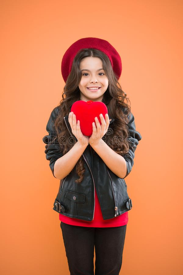 Love is in the air. parisian fashion girl hold red heart. world heart day. love. valentines day. child on yellow wall. Small girl kid with long curly hair stock photography
