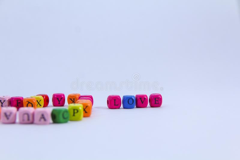 Love alphabet written on colourful wooden block with white background royalty free stock image
