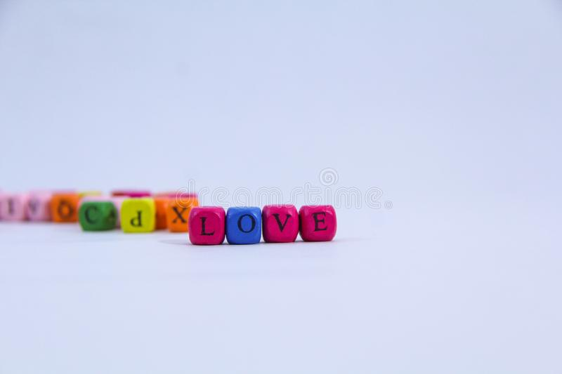 Love alphabet written on colourful wooden block with white background royalty free stock images