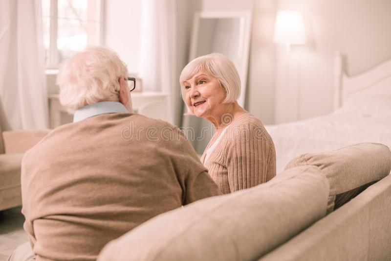 Kind female enjoying pleasant communication with her man. In love. Amazing senior women expressing positivity while looking at her husband royalty free stock image