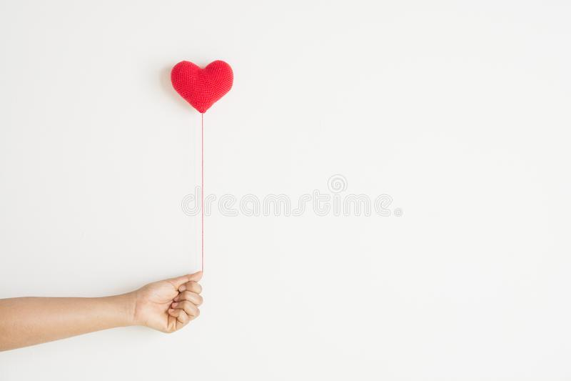 Love background, hand holding red heart knitting. Shape on white background royalty free stock images