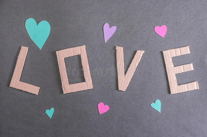 Love background. Real cut out of paper hearts around cardboard letters forming the word love for your romantic concepts stock photo
