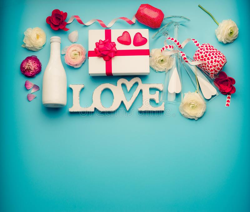 Love background. Various objects : bottle of champagne, gift box, ribbon, flowers, bow, glasses and hearts on light blue desktop stock image
