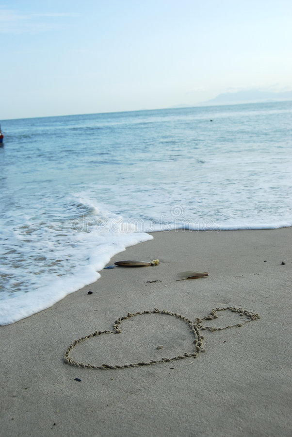 LOVE ON THE BEACH. Drawing on the sand - Love stock image