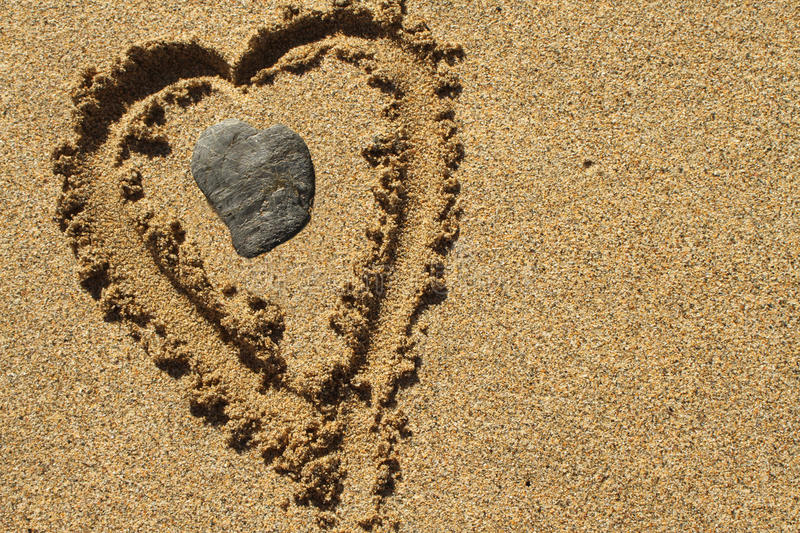 Love the beach. Love heart in stone and in the sand on a warm, sunny beach royalty free stock images